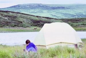 Patty near tent across lake caribou